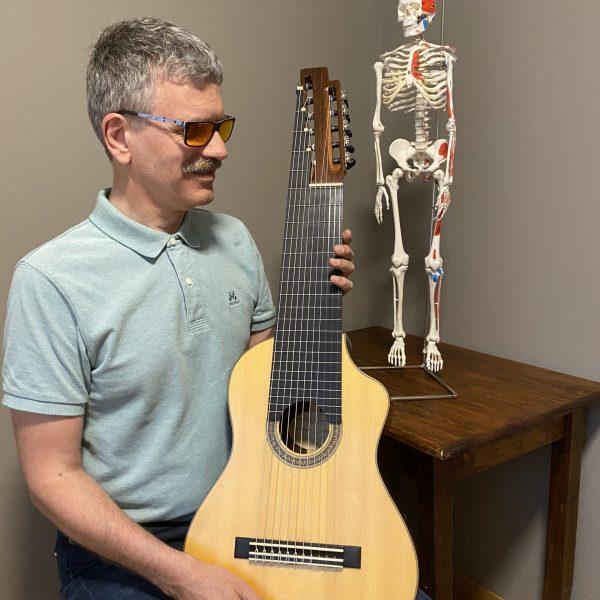 Bilde av Einar Fagerheim sittende med en 11-strengs gitar i fanget. I bakgrunnen står et miniskjelett på et bord.